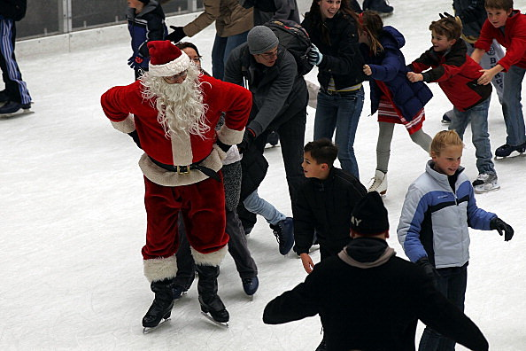 Skating Santa Entertains Holiday Tourists At New York's Rockefeller Center Ice Rink